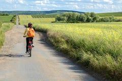Passeio do ciclista da mulher da vista traseira na bicicleta Fotos de Stock Royalty Free