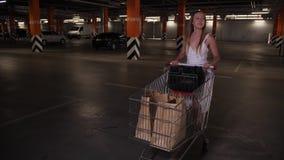Passeio fêmea com o carrinho de compras com o estacionamento filme