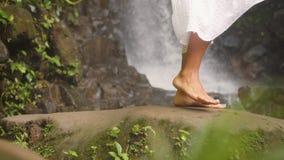 Passeio fêmea com os pés descalços na cachoeira natural bonita na selva tropical Curso calmo e despreocupado 4K do estilo de vida vídeos de arquivo