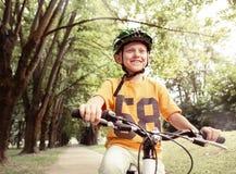 Passeio feliz do menino uma bicicleta no parque da cidade Imagens de Stock