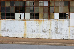 Passeio inclinado ao lado das janelas quebradas da fábrica Fotografia de Stock