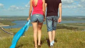Passeio masculino e fêmea no prado alto do monte do verão - conceito de viagem filme
