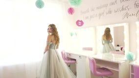 Passeio modelo da mulher bonita atrativa nova profissional lentamente em torno da sala clara pastel do salão de beleza no vestido filme