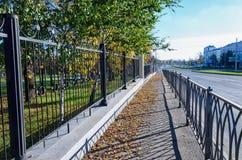 Passeio na cidade para pedestres entre as cercas do metal Imagens de Stock Royalty Free