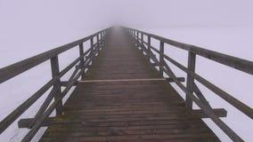 Passeio na ponte de madeira velha vazia do lago do inverno e na névoa escura da névoa da manhã video estoque