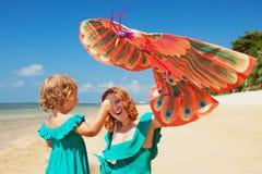 Passeio no papagaio do lançamento da mãe e da criança da praia do oceano Imagens de Stock