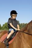 Passeio novo do menino um cavalo fotografia de stock