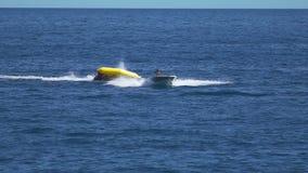 Passeio rápido super do barco de banana, pessoa que aprecia a atração extrema da água no verão vídeos de arquivo