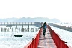 Passeio sobre a ponte vermelha de madeira através do mar no golfo de Tha fotografia de stock