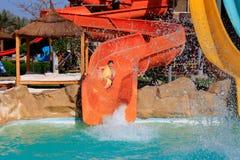 Passeios alegres do menino no parque da água Imagens de Stock Royalty Free