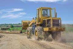 Passeios amarelos da escavadora na estrada da areia Fotos de Stock