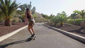 Passeios bonitos da moça na estrada perto da praia e das palmeiras no longboard no movimento lento vídeos de arquivo