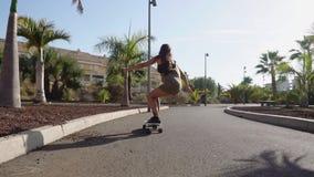 Passeios da moça na estrada perto das palmeiras no longboard no movimento lento video estoque