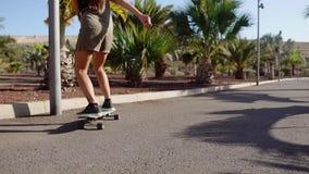 Passeios da moça na estrada perto das palmeiras no longboard no movimento lento filme