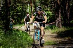 Passeios do ciclista através da floresta Imagens de Stock