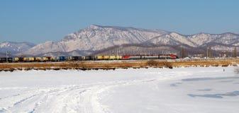 Passeios do comboio de mercadorias em um fundo das montanhas fotos de stock