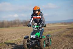 Passeios do menino no quadrilátero bonde de ATV Fotografia de Stock