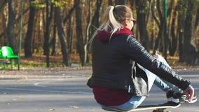 Passeios do skater da menina que sentam-se na placa e nos risos filme