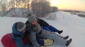 Passeios felizes da família e snowtube de sorriso em estradas nevado Movimento lento Paisagem do inverno da neve Fora esportes filme