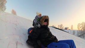 Passeios felizes da família e snowtube de sorriso em estradas nevado Movimento lento Paisagem do inverno da neve Fora esportes vídeos de arquivo