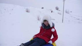 Passeios felizes da menina com pires e risos da neve Criança que sledding no inverno e no sorriso Resort de montanha Feriados do  filme