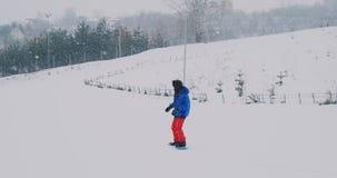 Passeios masculinos do snowboarder em uma placa na neve da inclinação do esqui no movimento lento filme