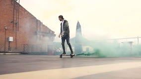 Passeios skateboarding do indivíduo considerável do moderno com fumo colorido no terraço da construção industrial Skater que faz  video estoque