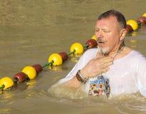 Passen de op middelbare leeftijd van de mensenpelgrim in de Rivier Jordan Baptism in Jordanië royalty-vrije stock foto's