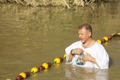 Passen de op middelbare leeftijd van de mensenpelgrim in de Rivier Jordan Baptism in Jordanië stock afbeelding