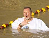 Passen de op middelbare leeftijd van de mensenpelgrim in de Rivier Jordan Baptism in Jordanië royalty-vrije stock afbeelding