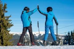 Passen Sie das Händchenhalten zusammen, das mit Skis auf die Gebirgsoberseite steht Stockbilder