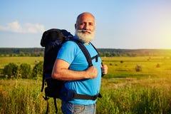 Passen Sie den gealterten Touristen, der mit Rucksack gegen Feldhintergrund steht Stockfotografie