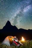 Passen Sie die Wanderer zusammen, die nahe dem glühendem Zelt und Lagerfeuer sitzen und zum sternenklaren Himmel des Glanzes im K Lizenzfreie Stockbilder