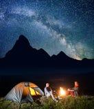Passen Sie die Wanderer zusammen, die nahe Lagerfeuer sitzen und zur Kamera unter unglaublich schönem sternenklarem Himmel Nachtd Lizenzfreies Stockbild