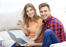 Passen Sie Studenten mit einem Laptop zusammen, der auf Sofa sitzt Stockfoto