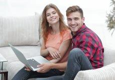 Passen Sie Studenten mit einem Laptop zusammen, der auf Sofa sitzt Lizenzfreie Stockfotografie