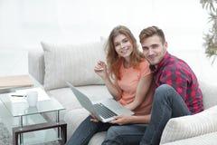 Passen Sie Studenten mit einem Laptop zusammen, der auf Sofa sitzt Stockfotos