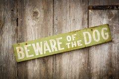 Passen Sie vom Hundezeichen auf altem getragenem hölzernem Zaun auf Stockfoto