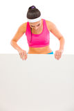 Passende Frau in der Sportkleidung, die auf unbelegter Anschlagtafel schaut Lizenzfreie Stockfotos