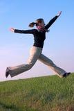 Passende schöne junge Frau, die in den Himmel springt stockfotografie