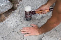 Passende Steinplatte des Gärtners in der Pflasterung mit einem Gummiholzhammer Stockfoto