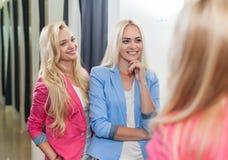 Passender Raum-Mode-Shop der jungen Frauen-zwei, der Spiegel, glückliche lächelnde blonde Mädchen versuchen das neue Kleidungs-Ei Stockbilder