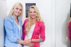Passender Raum-Mode-Shop der jungen Frauen-zwei, glückliche lächelnde blonde Mädchen, die das neue Kleidungs-Einkaufen versuchen Stockfotografie