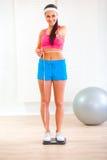 Passendes Mädchen auf Gewichtskala und -c$messen ihrer Taille Stockfotografie