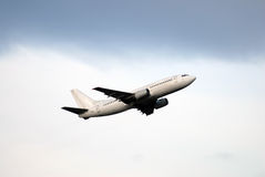 Passenger aircraft. Regional passenger airplane few moments after take-off, gradient sky, blur clouds stock images