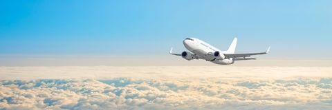 Passenger aircraft cloudscape with white airplane is flying in the daytime sky overcast, panorama view. Passenger aircraft cloudscape with white airplane is stock image