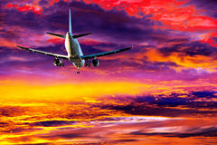 Passenger aircraft on colorful sky Stock Photos