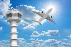 Passenger aircraft  flying above air traffic control tower agai. Nst blue sky Royalty Free Stock Photography