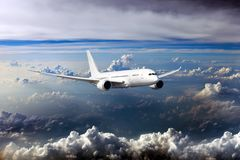Civil wide-body plane in the sky. Passenger aircraft flying on a high altitude above the storm clouds. Front view of airplane Royalty Free Stock Image