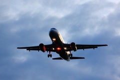 Passenger aircraft landing. Passenger Airplane coming in for landing on cloudy evening Stock Photos